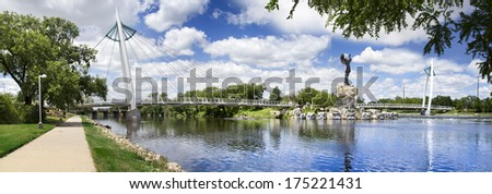 This is a photo of the Keeper Of The Plains statue and foot bridge across the Arkansas River near downtown in Wichita, Kansas.  - stock photo