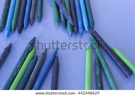 This is a photograph of Blue,Green and Purple crayons placed on colorful craft paper