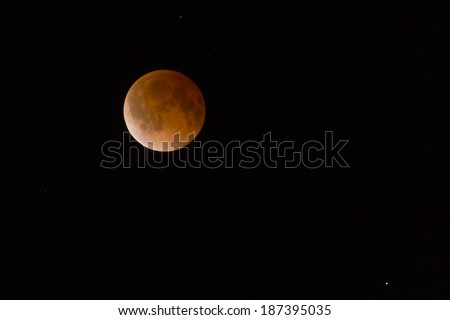 This is a photograph of the Lunar Eclipse Blood Moon Tetrad moving out of its maximum stage at 3:00 am Central Time United States. - stock photo
