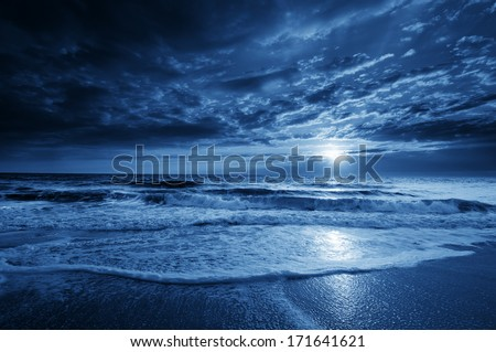 This is a photographic illustration of a beautiful midnight blue ocean moonrise along the coast with dramatic sky and rolling waves. - stock photo