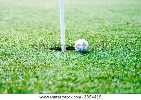 This is a picture of a golf ball next to the hole with flag pole showing. selective focus is on the ball and hole. - stock photo