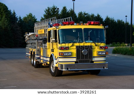 This is a picture of the front of a yellow fire truck used for reaching fires in high places, such as, tall office buildings. - stock photo