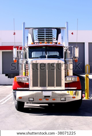 This is a picture of 18 wheeler refrigerated semi truck loading at a warehouse building dock. - stock photo