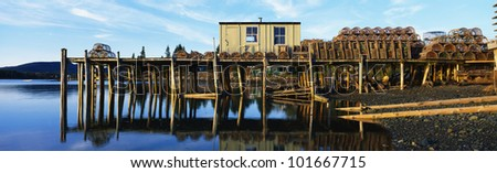 This is a pier with a small square wooden shack. There are lobster traps stacked up on the pier. - stock photo