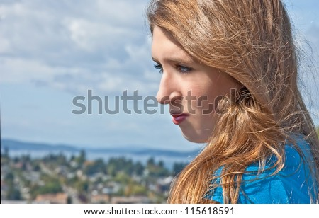 This is a portrait of a pretty Caucasian 17 year old teen girl.  She's outdoors and it's a head and shoulders from the side view.  Model has a wholesome look with light brown, long hair and blue eyes. - stock photo
