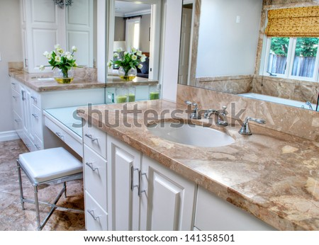 This is a pretty and contemporary bathroom with large vanity and sink areas in neutral colors.  Floor is a marble and cabinets a shade of white. - stock photo