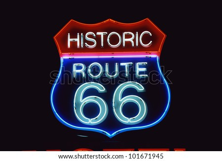 This is a road sign that says Historic Route 66. It is a neon sign in red, white and blue against a black night sky. - stock photo