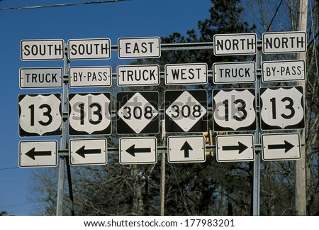 This is a set of road signs offering directions at a fork in the road. It points out the direction to travel on Interstate 13 North or South or 308 going east or west.  - stock photo
