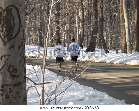 This is a shot of two runners training on a country road. - stock photo