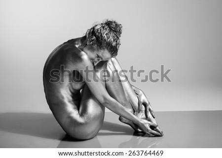 This is a side view of a female model, painted with silver body paint, including her hair and face, sitting on a white plexiglas background.  - stock photo