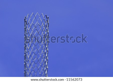 This is a stent in front of blue background. A stent is a small mesh tube that's used to treat narrowed or weakened arteries in the body.