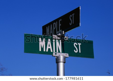 This is a street sign labeling the corner of Main Street & Maple Street. The sign is green with white lettering against a blue sky. - stock photo
