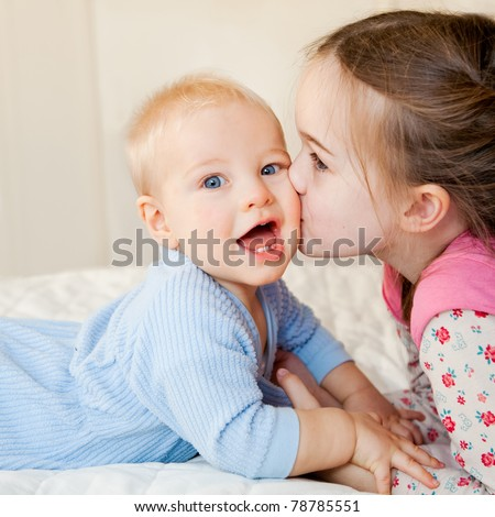 This is a sweet moment between a big sister and her baby brother.  The baby is looking at the camera with a look of delight.  The sister is kissing his cheek. - stock photo