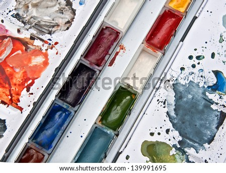 This is a tray of watercolor paints both in pans and mixed on a palette side of an artist's materials and tools. - stock photo