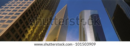 This is a view looking up at the office towers in Los Angeles. Light glistens on the side of the buildings. - stock photo