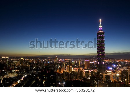 This is a view of Taipei City just after sunset.  The tall building is Taipei 101 and the area around it is the commercial district