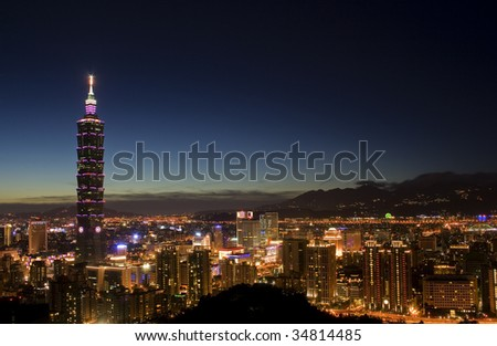 This is a view of Taipei City just after sunset.  The tall building is Taipei 101 and the closest area is Taipei commercial district.