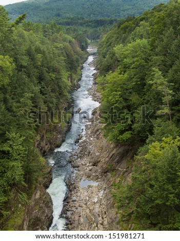 This is a view of the Ottauquechee River flowing through the Quechee Gorge State Park. - stock photo