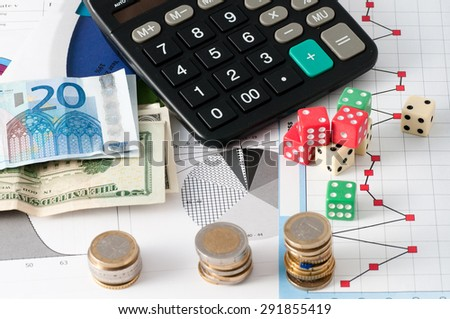 This is a view with the dice game and the game in play the stock market with finance graphs, coins and banknotes - stock photo