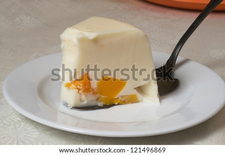 This is a wedge of jelly cake. The cake contains cream and peaches. - stock photo