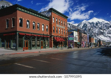 This is a western town front in the winter. There are snow covered mountains in the background with red bricked buildings in the foreground. - stock photo