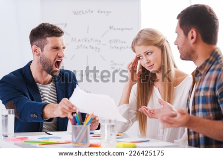 This is all wrong! Two frustrated business people sitting at the table and gesturing while their furious boss holding paper and shouting  - stock photo