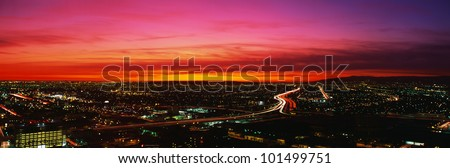 This is an aerial view of downtown Los Angeles at sunset. The streaked lights of the freeway are in the center with an orange sunset sky. - stock photo