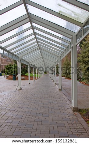 This is an empty covered walkway with brickwork on the ground on a cloudy, overcast day in a city. - stock photo