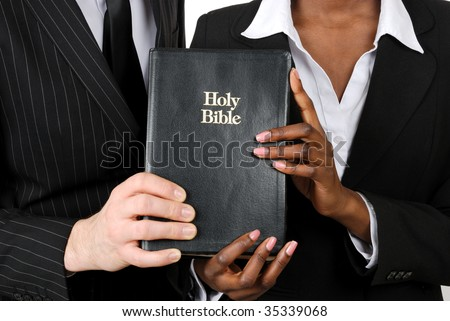 This is an image of a business couple holding a bible. - stock photo