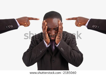 This is an image of a man feeling guilty, with two fingers pointing at him. He is at the centre of blame. - stock photo