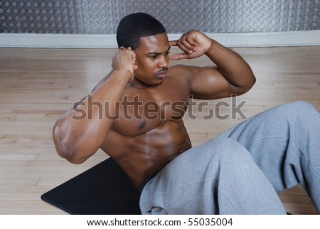 This is an image of a man performing sit ups. - stock photo