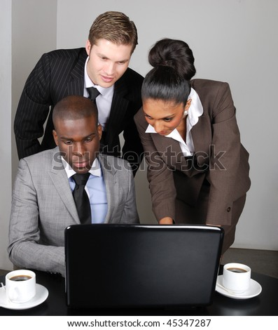 This is an image of a multi ethnic business team working on laptop. - stock photo