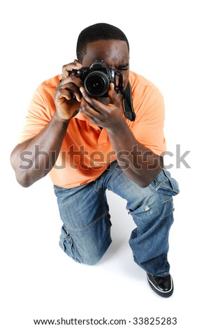 This is an image of a student photographer kneeling to take a picture with a camera.