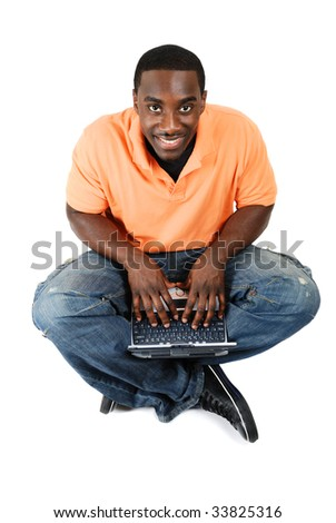 This is an image of a young student sitting and using his laptop.