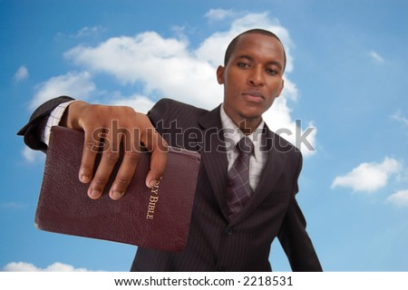 "This is an image of man holding a bible. This image can be used to represent ""Heavenly message"", ""sermon"", ""preaching"" etc..."