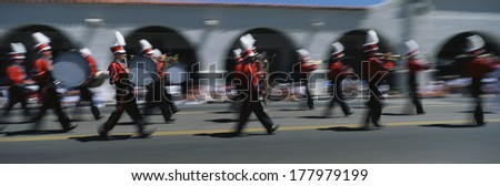 This is an Independence Day Parade in a small town. It shows patriotism and a piece of Americana. This is a marching band with tall shaker hats and musical instruments. - stock photo