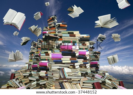This is books mountain. Many books on background of white clouds and blue sky.