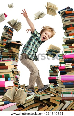 This is books scramble. Happy little boy is young reader which is jumping between high piles of books.