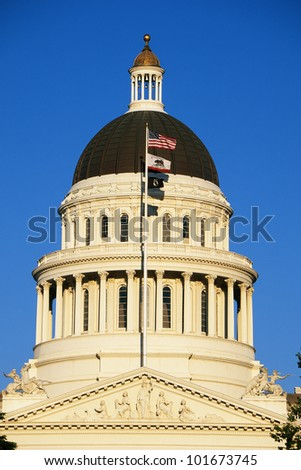 This is California's State Capitol dome at sunset. It has several flags waving in the wind on a flagpole in front of it. - stock photo