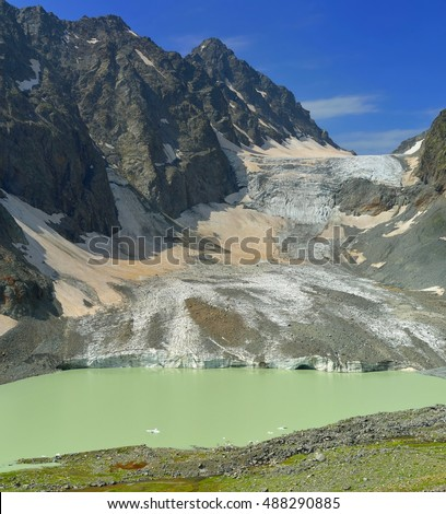 This is colorful colorful glacier and green lake in Caucasus mountains
