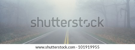This is Fossy Road in a fog.  It signifies hazardous driving conditions as you can only see a few feet of the road and the way ahead is obscured by the fog. - stock photo