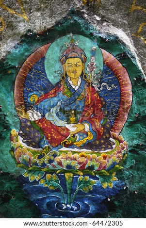 This is Guru Rinpoche, known as Second Buddha in Bhutan. Devout Buddhists painted many sacred images on rocks, this is just one of them. This is a generic painting, not copyrighted. - stock photo