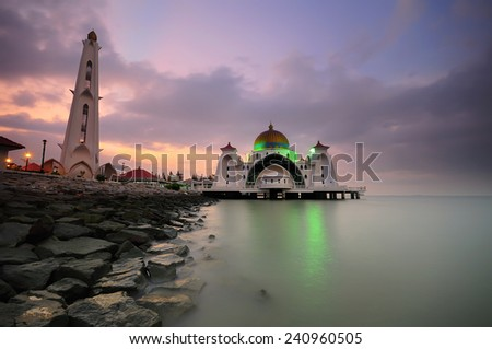 This is image of Malacca Straits Mosque (Masjid Selat Melaka) during sunrise. It is located at Malacca , Malaysia and also located in the Strait of Malacca, where it is a busy route in the world . - stock photo