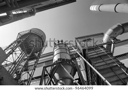 This is industrial object with flue gas stack. There are many metallic constructions on the photo. - stock photo