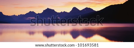 This is Lake McDonald. There is a reflection of the mountains in the lake. - stock photo