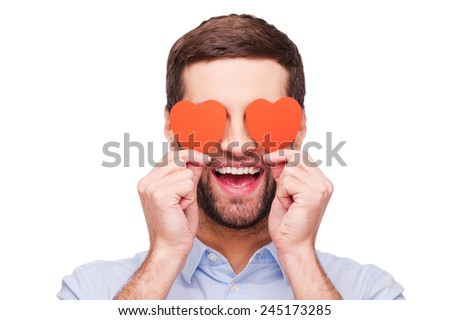 This is love! Handsome young man holding heart shaped valentine cards in front of his eyes and smiling while standing isolated on white background   - stock photo