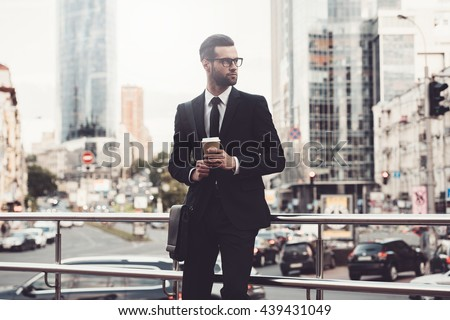 This is my city. Confident young man in full suit holding coffee cup and looking away while standing outdoors with cityscape in the background  - stock photo