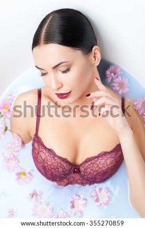 This is my pleasure. Attractive young woman is taking a herbal bath at home. She is lying and gently smiling. Her eyes are closed with enjoyment - stock photo
