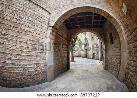 This is one of the entrances to Sant Felip Neri square, a calm, small place located (almost hidden) at the gothic quarter of Barcelona. We can also see part of the facade of Sant Felip Neri's church. - stock photo