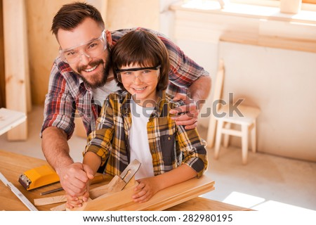This is our happy place. Happy young male carpenter teaching his son towork with wood in his workshop - stock photo